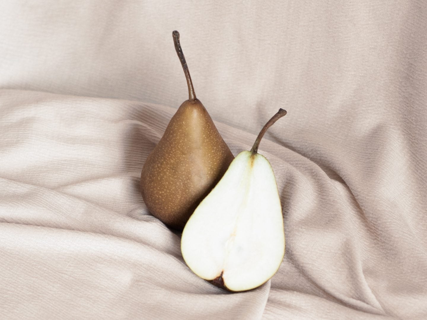 Two pears displayed on a woven blanket