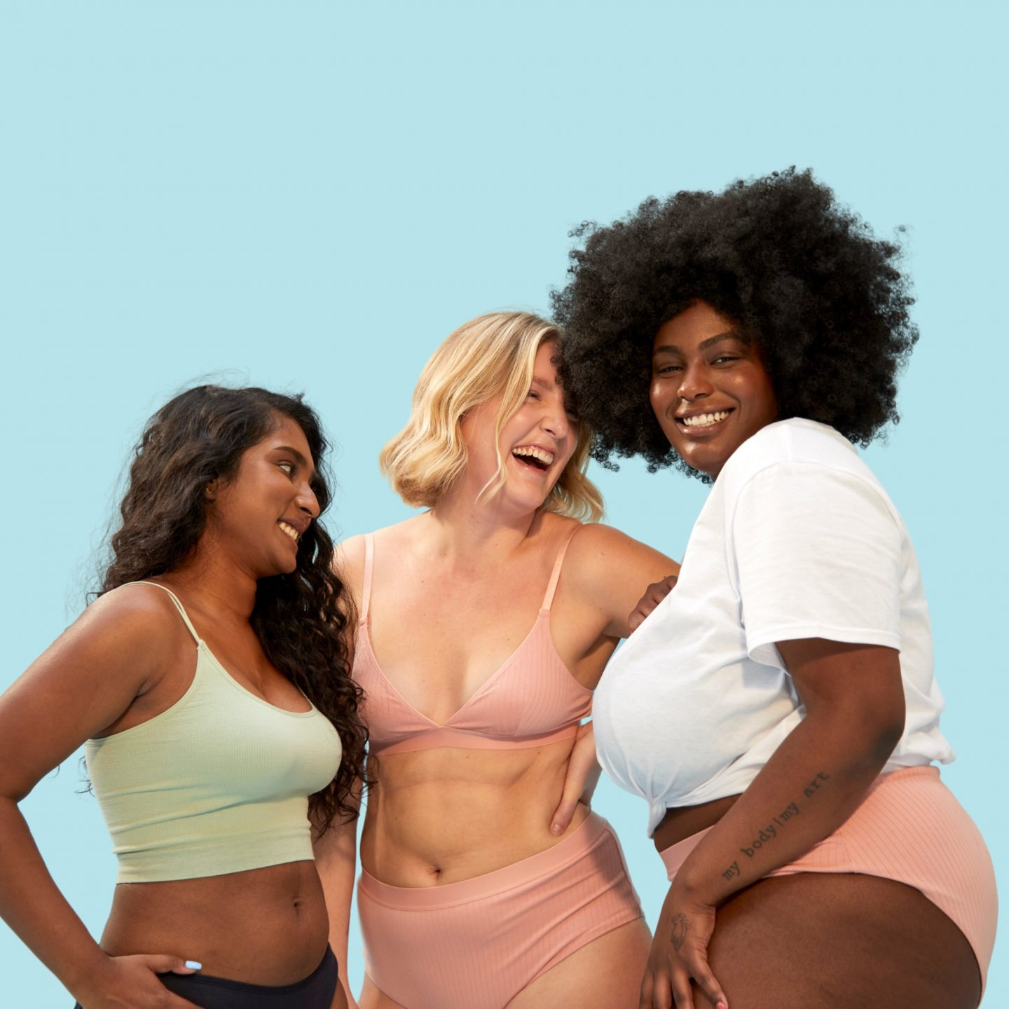 Three women wearing underwear laughing
