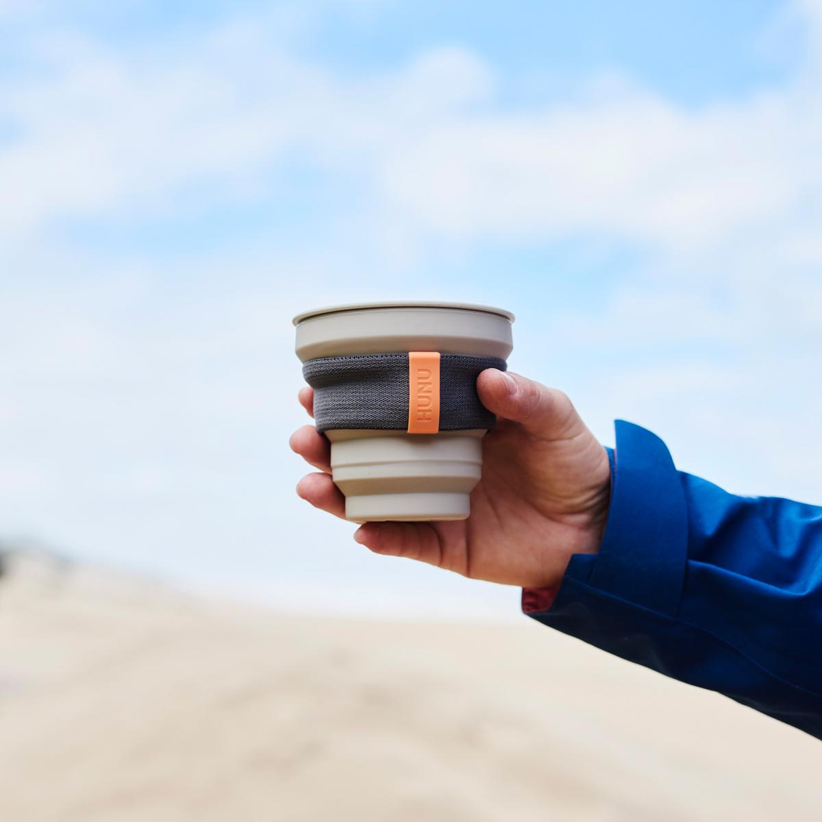 HUNU reusable cup held up in front of beach
