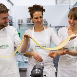 Three students holding fresh pasta at Cookery School