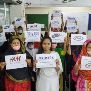 Female garment workers hold up signs for PayYourWorkers